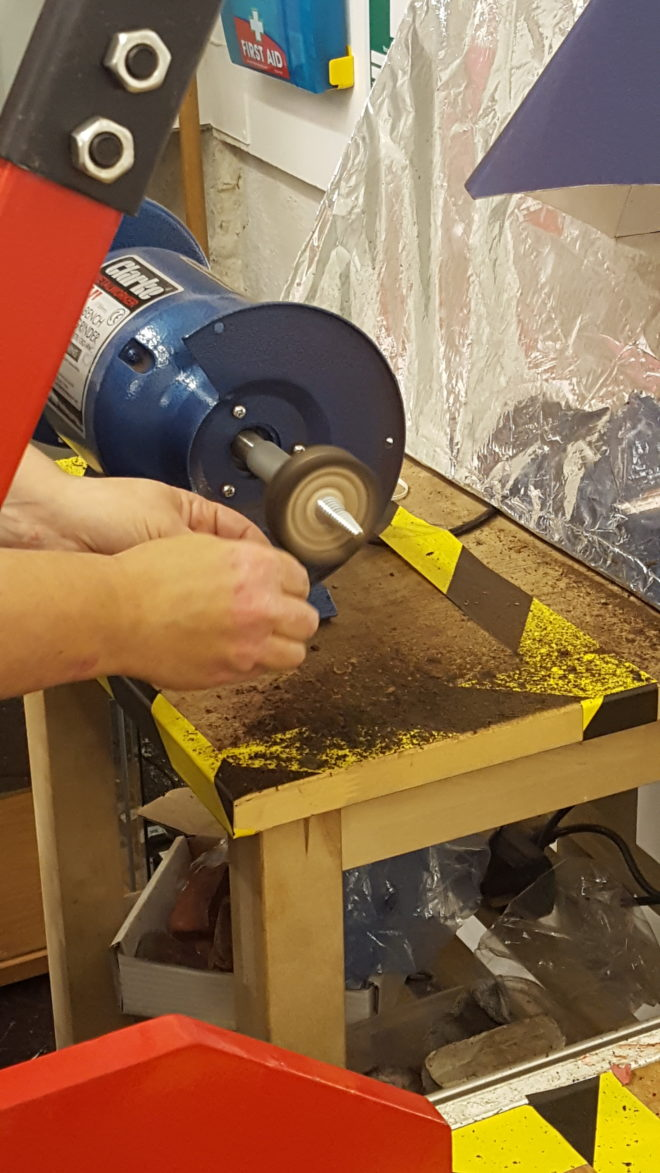 using the grinder to polish our rings to give a smooth finish to the ring surface