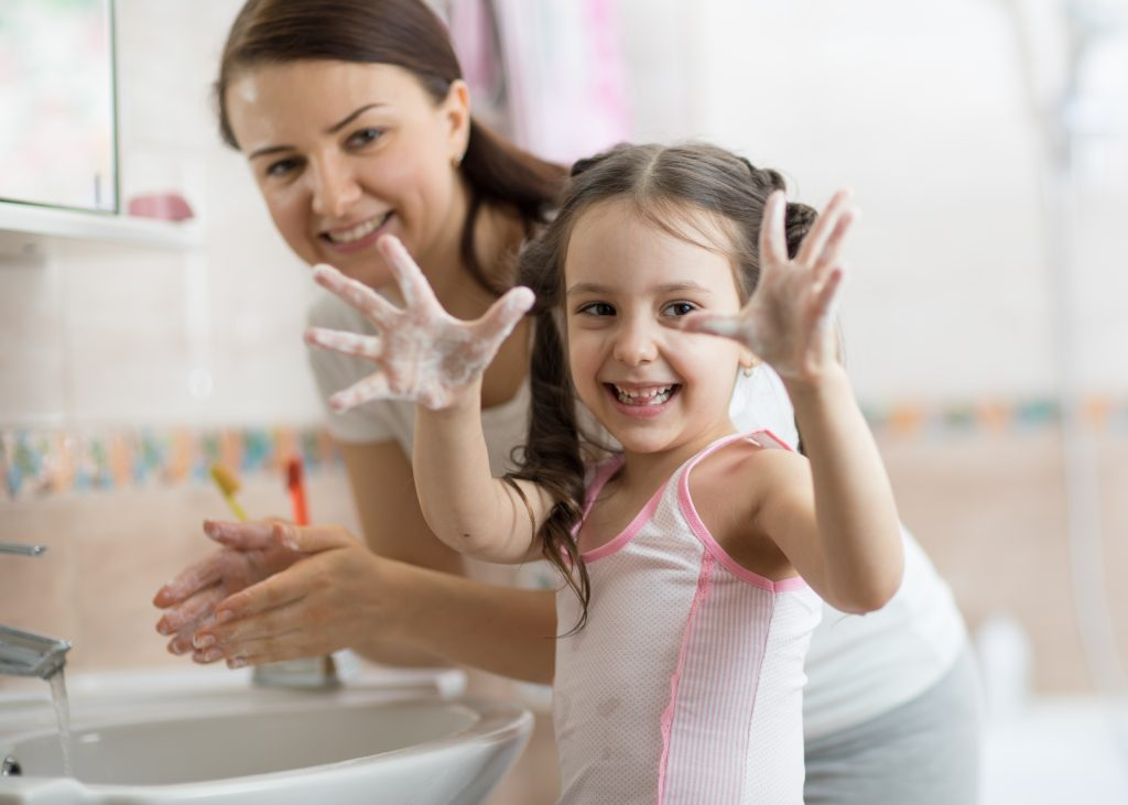 Mother and daughter learning how to wash their hands accurately