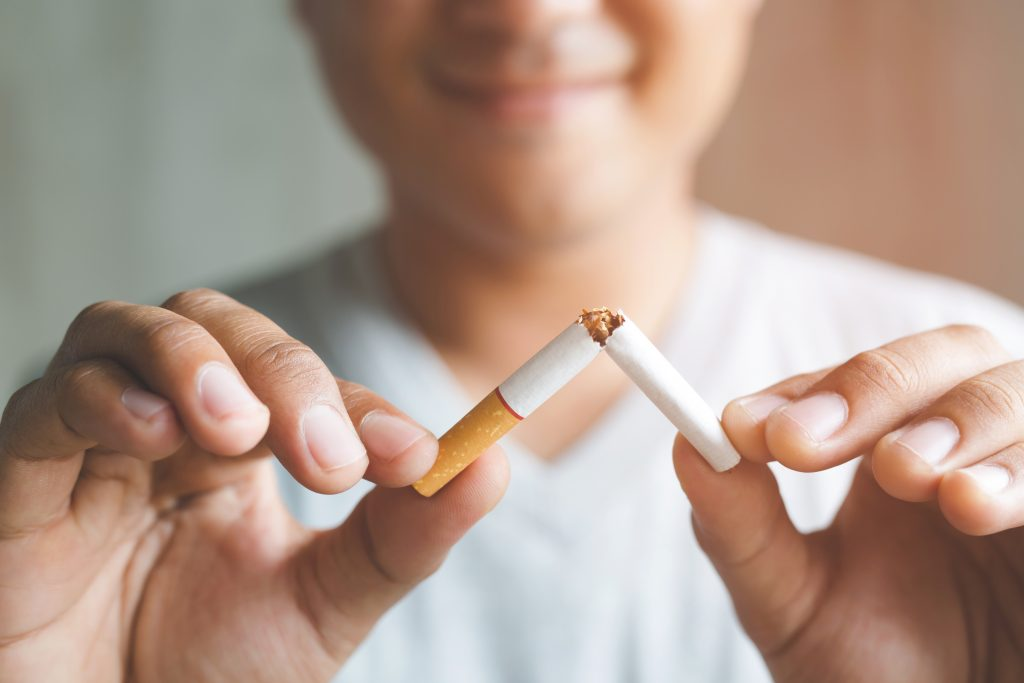 Man snapping cigarette in half as he quits to boost his immune system