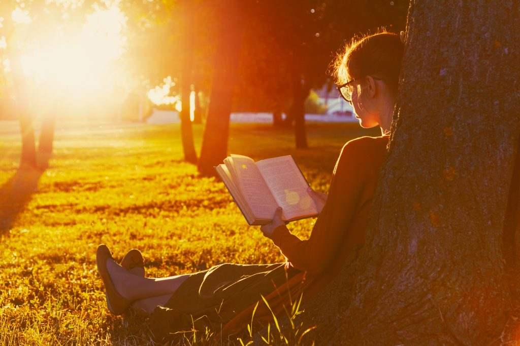 A woman reading in a park as part of her summer bucket list