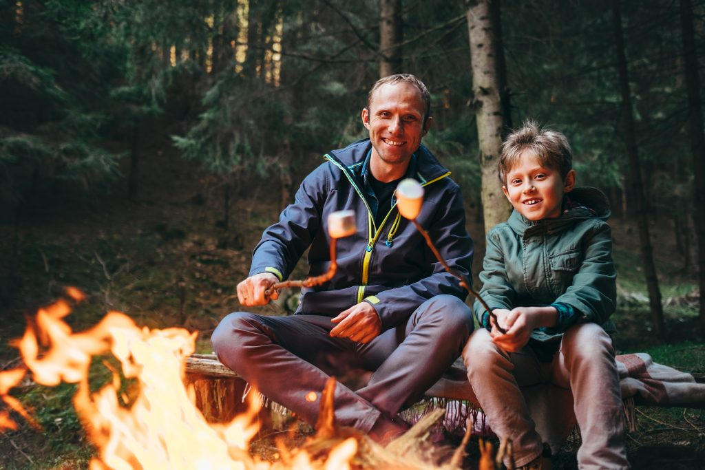 A father and son camping in the woods as part of their summer bucket list