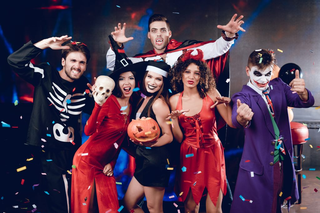 A group of 6 people from the same household ready to host a Zoom Halloween costume party with their friends.